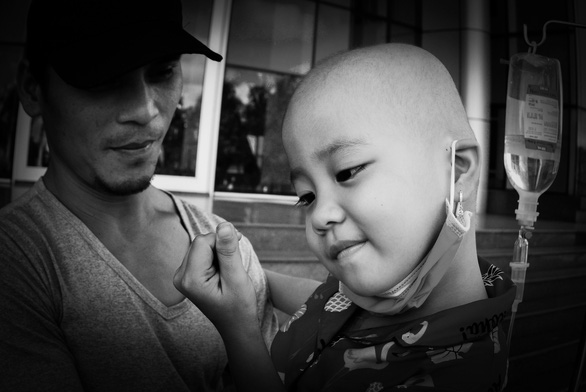 A child suffering from cancer shares his love. Photo: Dang Huu Hung