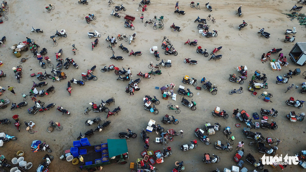 Buyers park their motorbikes and bicycles along the beach. Photo: Nam Tran / Tuoi Tre