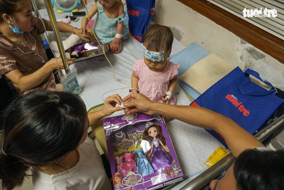 A girl gets a new doll right on her sickbed at an oncology hospital in Hanoi. Photo: Nguyen Hien / Tuoi Tre