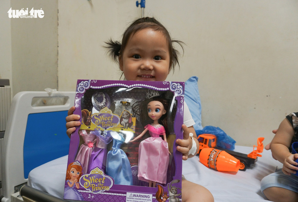 Three-year-old Bong smiles for a photo with her new doll at an oncology hospital in Hanoi. Photo: Nguyen Hien / Tuoi Tre