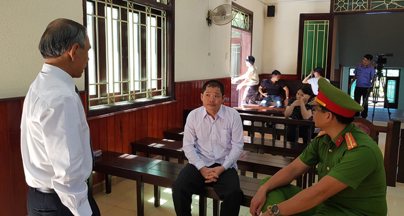 Le Quoc Binh speaks with his lawyer during a court in Binh Dinh Province, Vietnam on May 26, 2019. Photo: Duy Thanh / Tuoi Tre