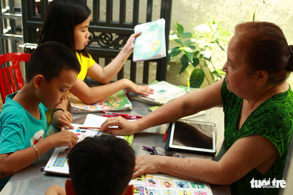 Tran Thi Huong tutors children at her home in Da Nang, Vietnam. Photo: Tan Luc / Tuoi Tre