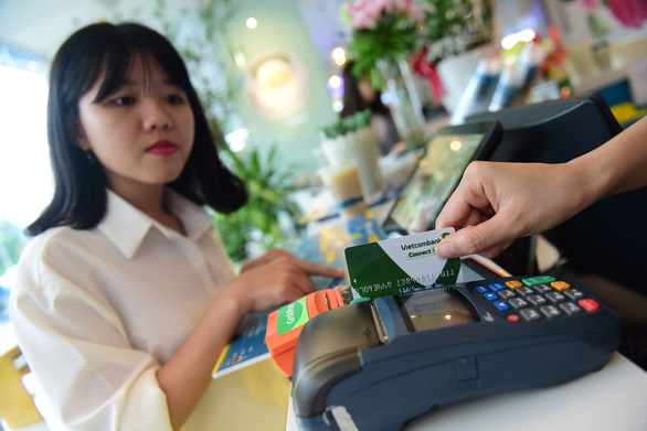 A store employee swipes a domestic bank card at a POS machine in Vietnam. Photo: Quang Dinh / Tuoi Tre