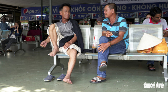Two men smoke on a bench at Mien Dong Bus Station in Binh Thanh District, Ho Chi Minh City. Photo: Duyen Phan / Tuoi Tre
