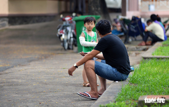 A man smokes next to his son at Children's Hospital 2 in District 1, Ho Chi Minh City. Photo: Duyen Phan / Tuoi Tre