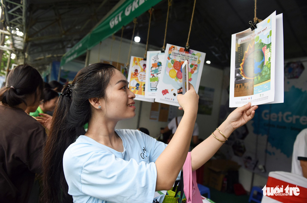 A woman takes a photo of a poster promoting environmental protection at Song Xanh Festival at Le Van Tam Park, District 1, Ho Chi Minh City, June 2, 2019. Photo: Duyen Phan / Tuoi Tre