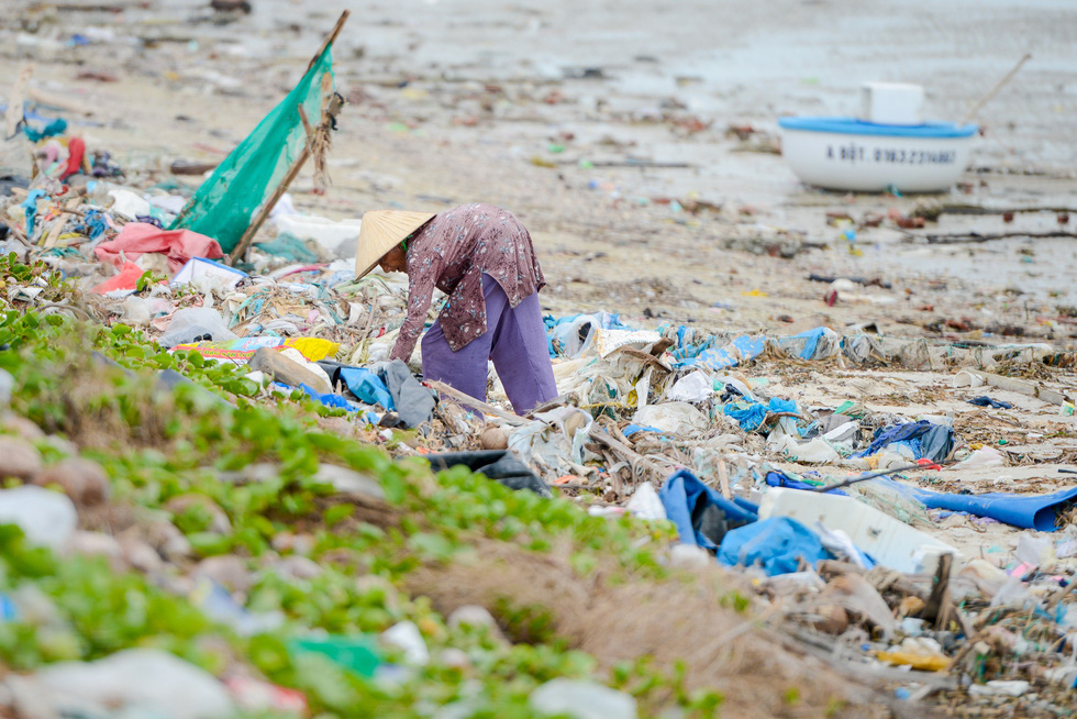 An elderly woman collects scraps along a trash-filled beach.