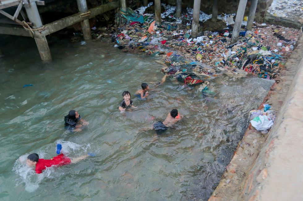 Children swim at a polluted beach.