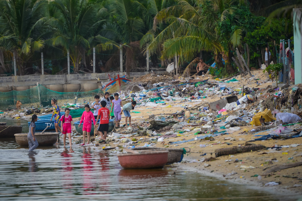 Children hang out at a trash-filled beach in the south-central province of Khanh Hoa.