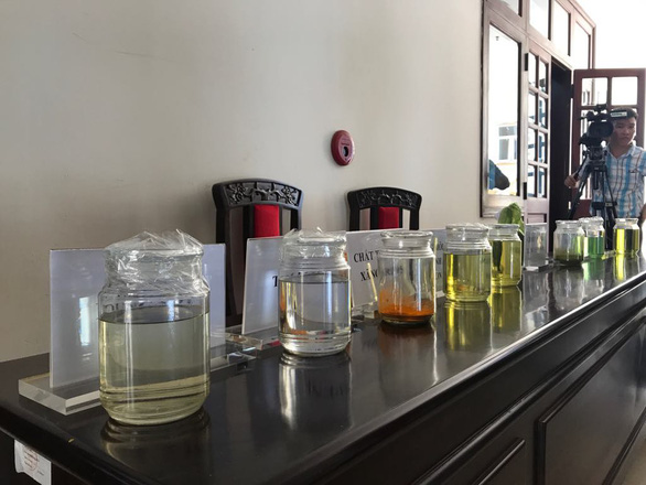 Samples of fake fuel and solution are displayed at the press conference. Photo: Trung Tan / Tuoi Tre