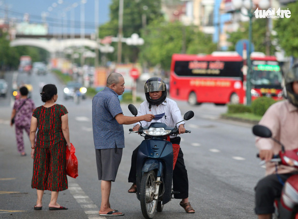 A black market reseller approaches a potential buyer in front of the Viet Tri Stadium, in the northern province of Phu Tho, on June 6, 2019. Photo: Nam Khanh / Tuoi Tre