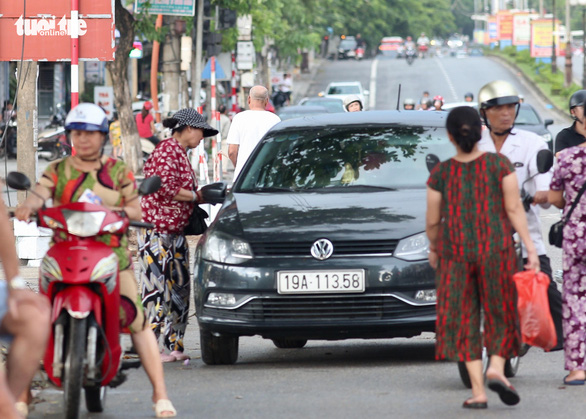 Black market resellers approach a potential buyer on a car in front of the Viet Tri Stadium, in the northern province of Phu Tho, on June 6, 2019. Photo: Nam Khanh / Tuoi Tre