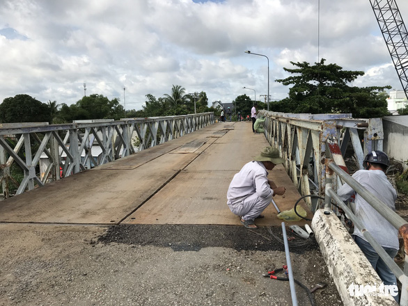 Workers reinstall damaged communications cable lines on the Tan Nghia Bridge in Dong Thap Province, Vietnam on June 7, 2019. Photo: Ngoc Tai / Tuoi Tre
