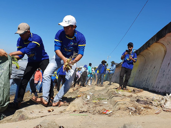 Members of the Vietnam Youth Federation and local youths collect garbage along a 700-meter long beach. Photo: Tran Mai / Tuoi Tre