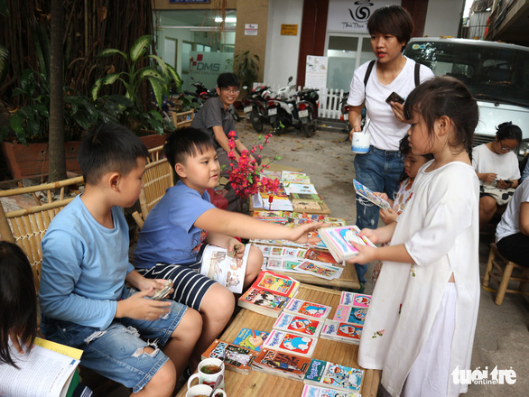 Children sitting by comic books at an extracurricular activity where parents try to encourage reading as a summer activity for children. Photo: Phuong Vy / Tuoi Tre