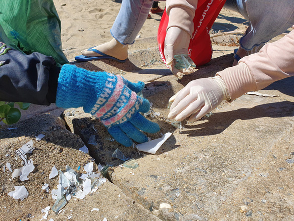 Volunteers carefully collect pieces of glass on the beach. Photo: Tran Mai / Tuoi Tre