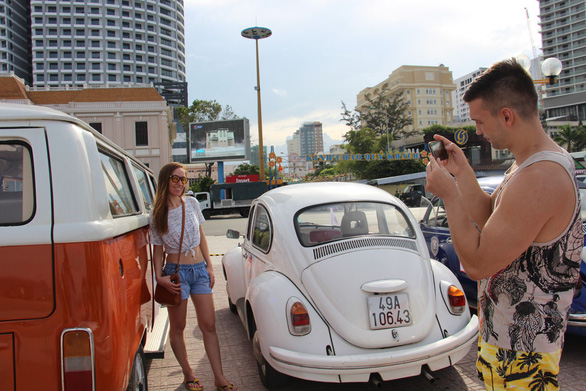 Visitors take photos with vintage automobiles in Nha Trang City, Vietnam on June 9, 2019. Photo: Thai Thinh / Tuoi Tre