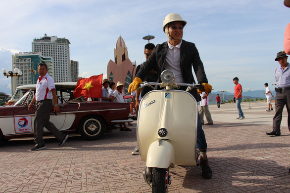 A visitor takes photos with a vintage Vespa scooter in Nha Trang City, Vietnam on June 9, 2019. Photo: Thai Thinh / Tuoi Tre