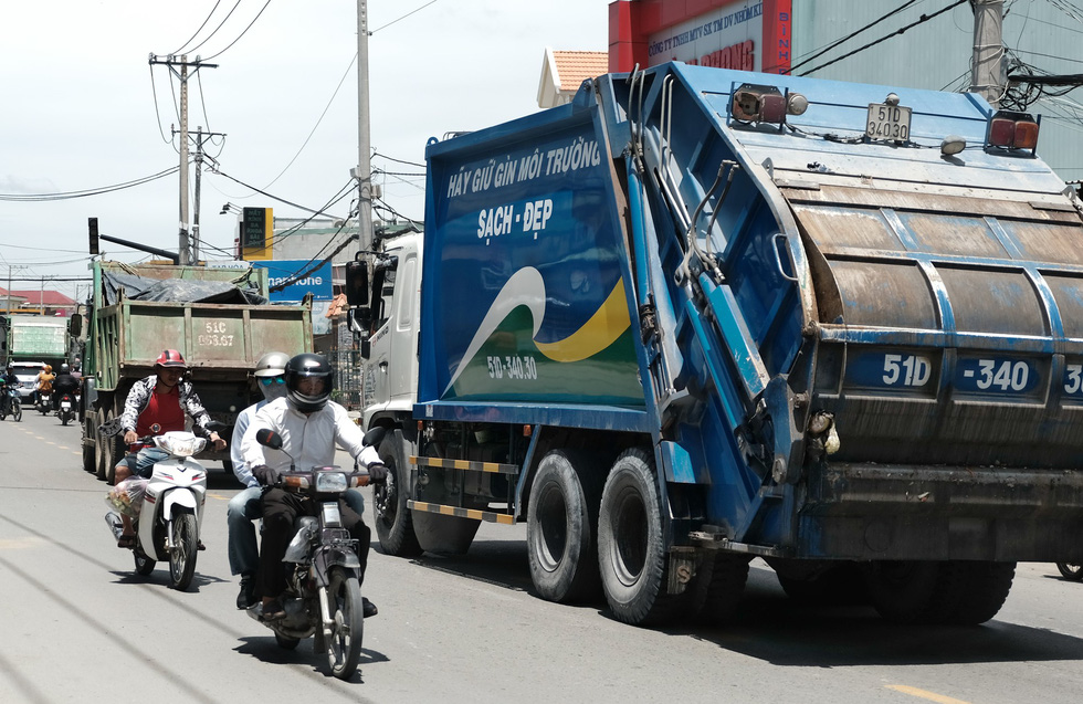 Garbage trucks move in a line on a street in Binh Chanh District, Ho Chi Minh City. Photo: Mai Thuong / Tuoi Tre