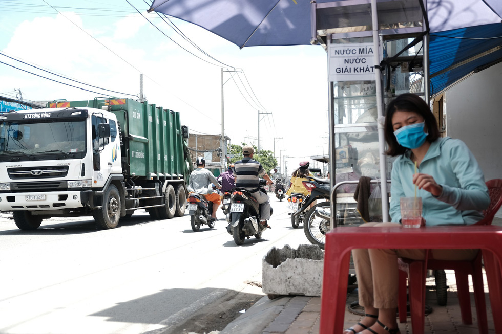 A woman wears a facemask while enjoying her drink as a garbage truck approaches on a street in Binh Chanh District, Ho Chi Minh City. Photo: Mai Thuong / Tuoi Tre