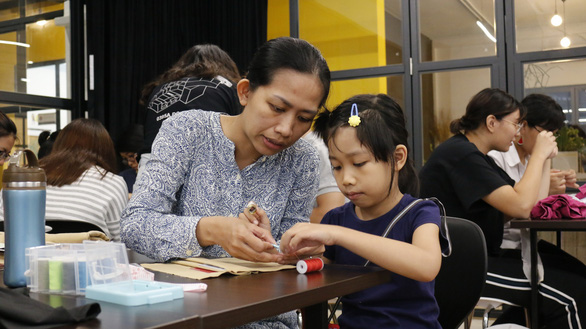 Gia Han (right) works on her wallet with her mother. Photo: Minh Nguyet / Tuoi Tre
