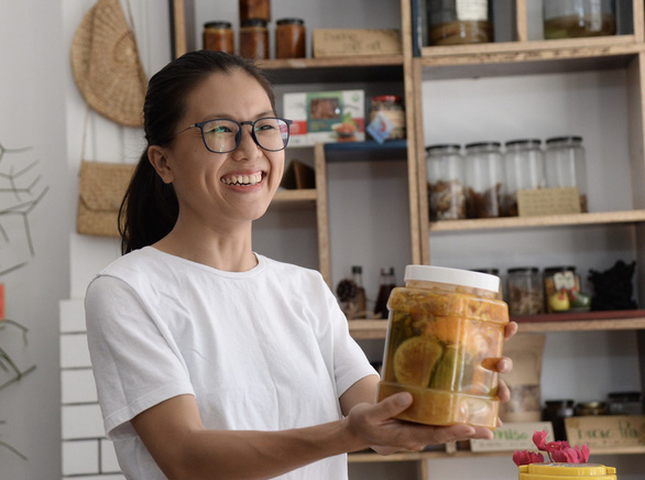 Phi Yen hands a container of organic food to customers at Co Eco Home in Ho Chi Minh City. Photo: Tu Trung/ Tuoi Tre