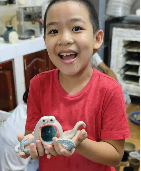 Nine-year-old Nguyen Nhat An expresses the excitement of holding his masterpiece at a pottery workshop in Ho Chi Minh City. Photo: Vu Thuy / Tuoi Tre