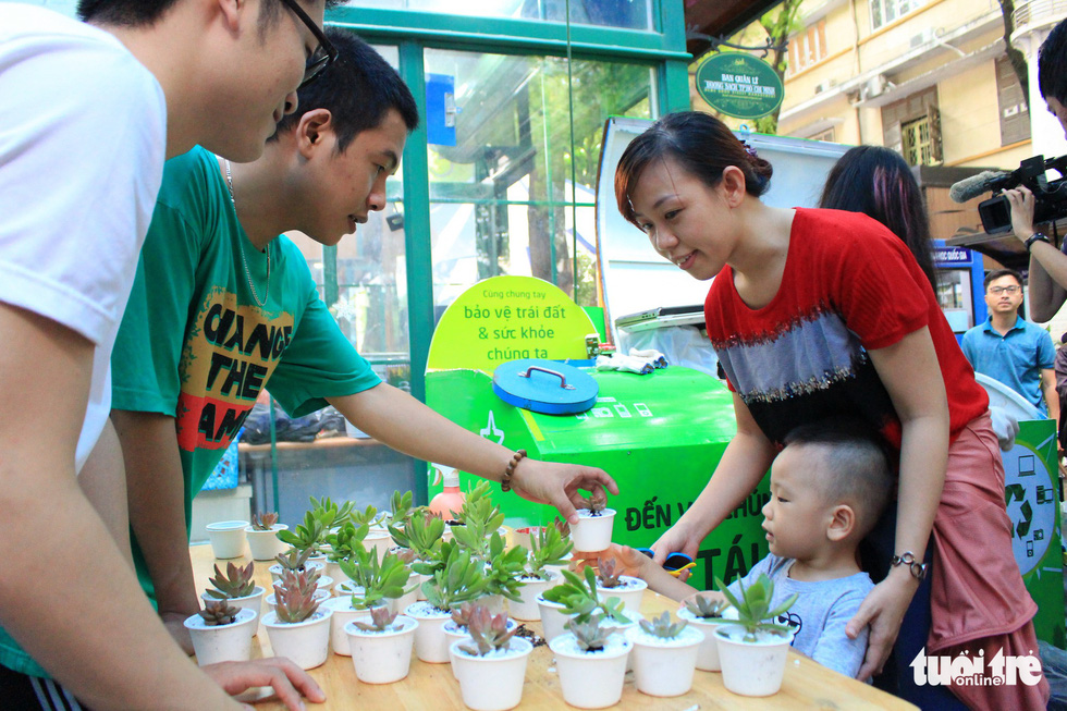 A woman with her son (right) choose a plant after they gave the organizing committee their electronic waste. Photo: Thanh Yen / Tuoi Tre