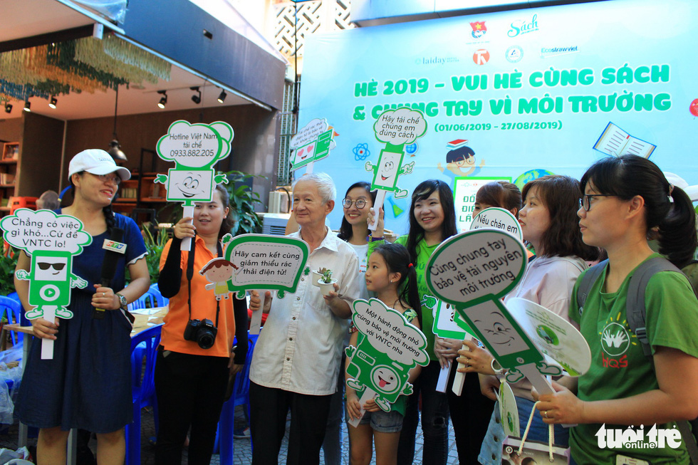 Participants take photo with organizing committee and slogans to protect the environment. Photo: Thanh Yen / Tuoi Tre