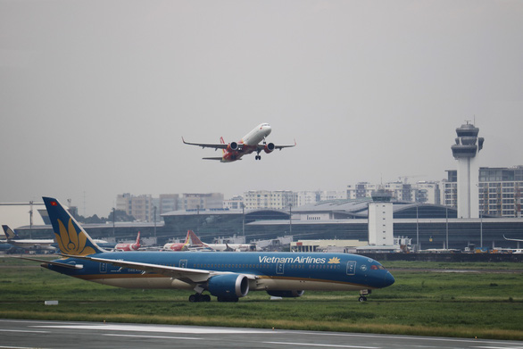 A Vietnam Airlines plane touches down while a Vietjet aircraft takes off from Tan Son Nhat International Airport, in Ho Chi Minh City. Photo: Ngoc Phuong / Tuoi Tre
