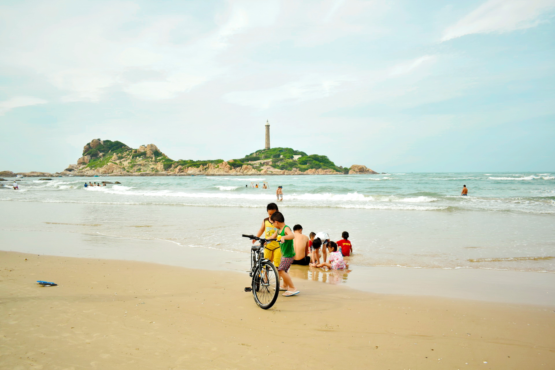 Beach-goers take a swim in the water at the Ke Ga Beach in Binh Thuan Province, Vietnam as the Ke Ga Lighthouse is seen in the background. Photo: Tuan Son / Tuoi Tre News