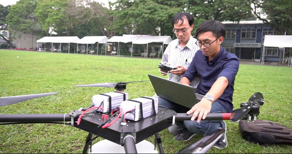 Two men test out the flying drone for pesticide application, built by a research group from the University of Technology – Vietnam National University Ho Chi Minh City. Photo: N.T. / Tuoi Tre