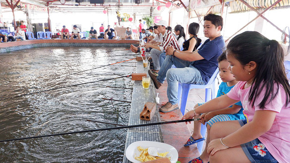 Parents and children take part in prawn fishing activity on water bus tour in Ho Chi Minh City. Photo: Kim Anh / Tuoi Tre