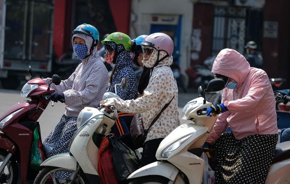 Vietnamese commuters protect themselves from the sun. Photo: Tuoi Tre