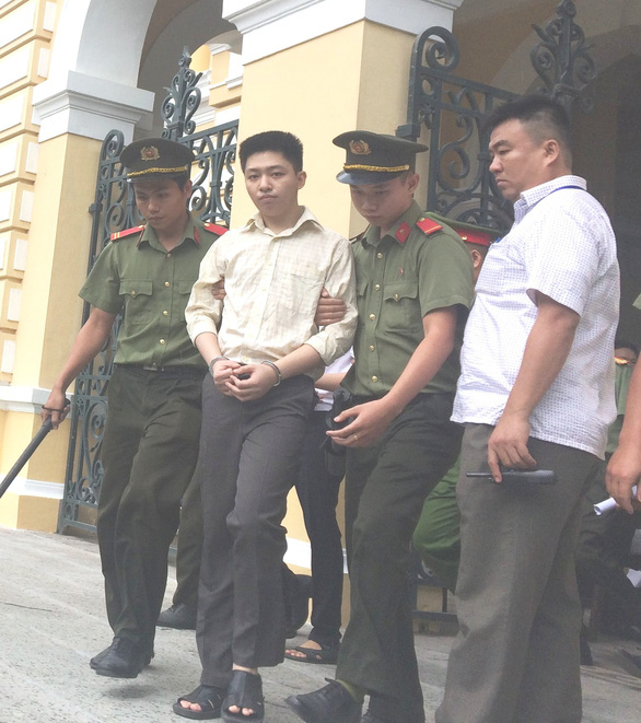Huynh Duc Thanh Binh, a 23-year-old college student, is seen being escorted by police officers at the People's Court of Ho Chi Minh City on June 24, 2019. Photo: Tuoi Tre