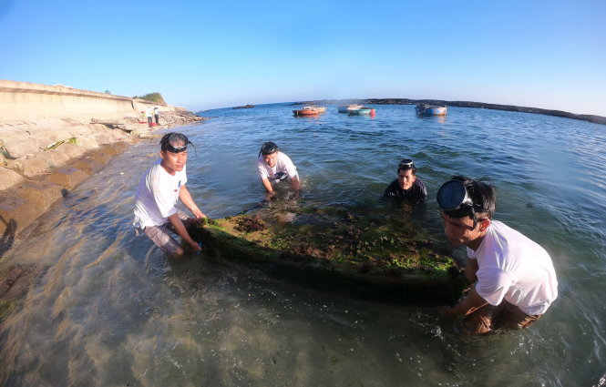 Islanders dive under the sea to collect hidden garbage thrown onto the beach. Photo: L.X.T / Tuoi Tre