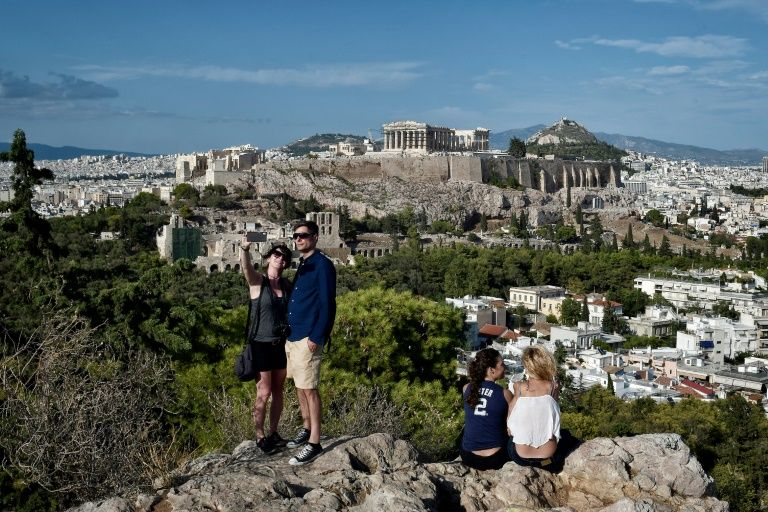 Tourists take a selfie with the Acropolis in the background. Photo: AFP
