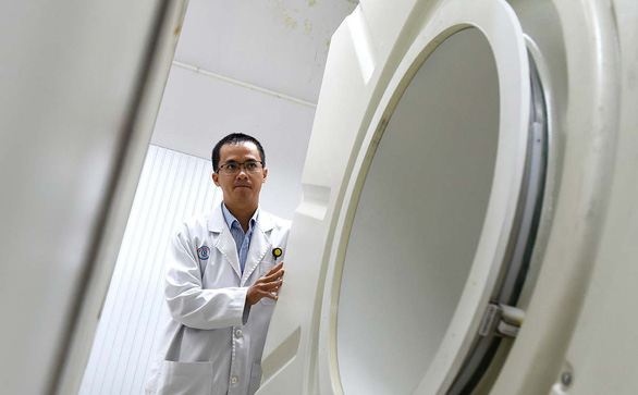 Nguyen Tan Chau is pictured next to the PET/CT scanning system at Cho Ray Hospital. Photo: Duyen Phan / Tuoi Tre
