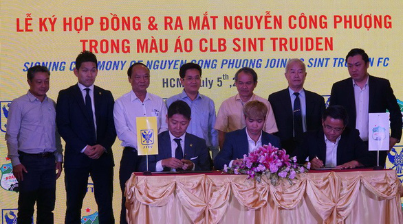 Vietnamese striker Nguyen Cong Phuong (sitting, middle) signs for Belgian first-division side Sint-Truiden at a ceremony in Ho Chi Minh City on July 5, 2019. Photo: Anh Dung / Tuoi Tre