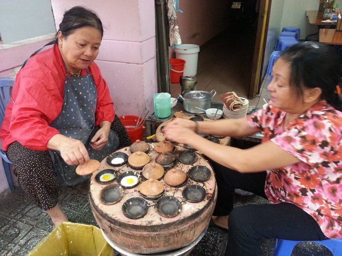 Two women cook banh can in Da Lat, Vietnam's Central Highlands. Photo: Huyen Tran / Tuoi Tre