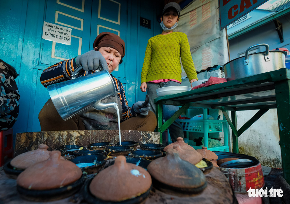A woman pours powder into a pancake pan to make banh can. Photo: Mai Vinh / Tuoi Tre