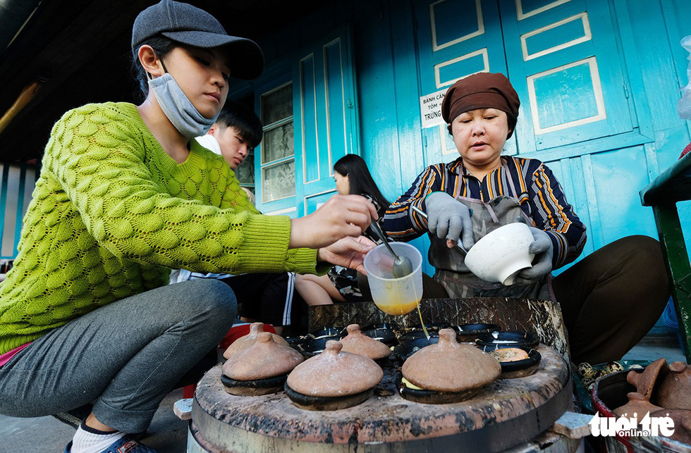 Two women cook banh can in Da Lat, Vietnam's Central Highlands. Photo: Mai Vinh / Tuoi Tre