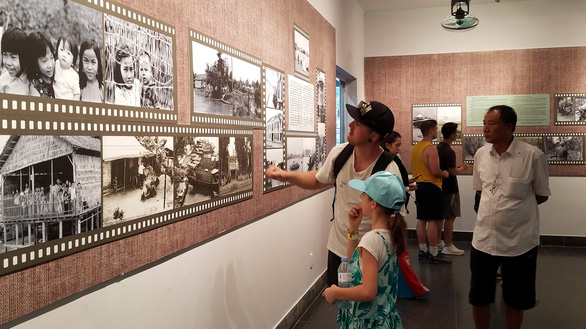 Visitors watch photos taken by Ignacio Ezcurra at the War Remnants Museum in Ho Chi Minh City on July 9, 2019. Photo: Lam Dien / Tuoi Tre