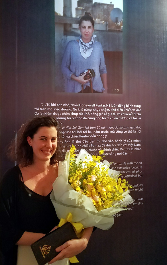 Luisa Duggan takes a photo in front of a poster introducing her at the Stories from a camera exhibition taking place the War Remnants Museum in Ho Chi Minh City on July 9, 2019. Photo: Lam Dien / Tuoi Tre