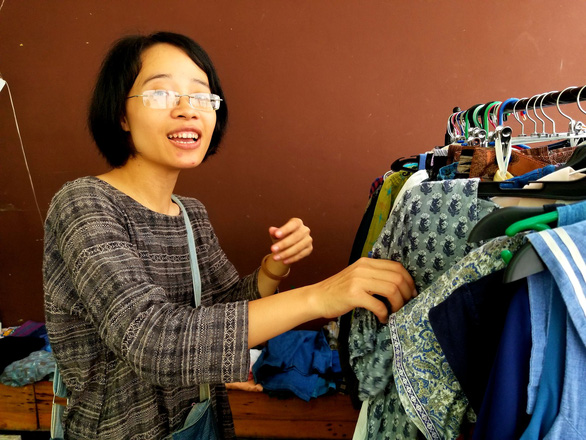 Le Thi Thu Huong at her secondhand clothes stall at the market. Photo: Ha Thanh / Tuoi Tre