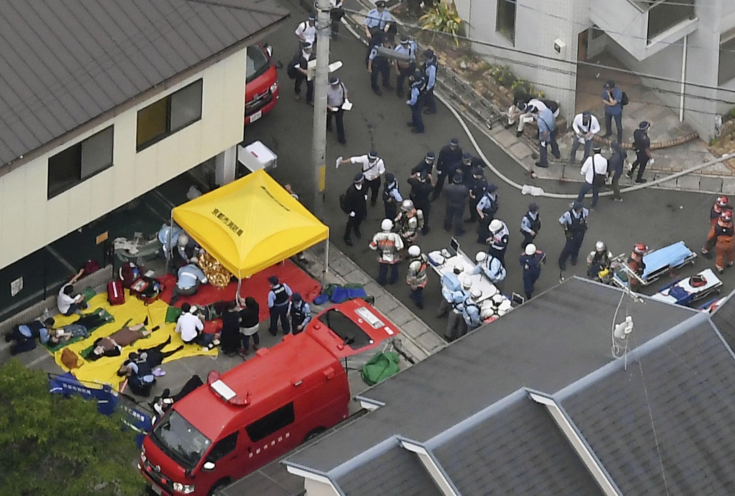 Rescue workers carry injured people from the three-story Kyoto Animation building which was torched in Kyoto, western Japan, in this photo taken by Kyodo July 18, 2019.