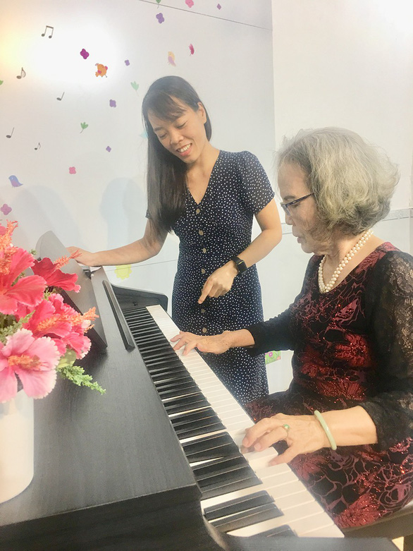 Nguyen Thi Lam, 80, learns to play the piano under careful instructions of the teacher. Photo: My Lang / Tuoi Tre