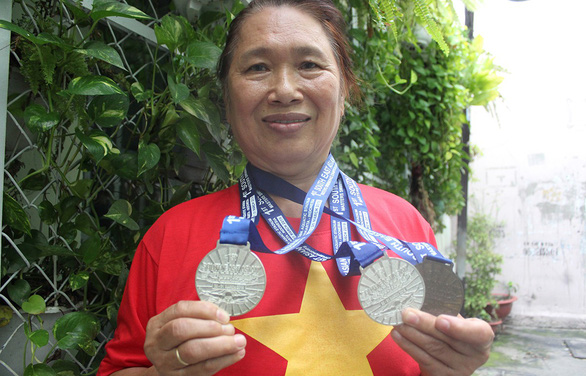 Tang Duy Ngoc holds two medals for swimming and smiles in pride. Photo: Tuoi Tre