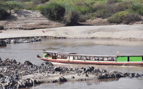 A boat travels on a nearly dried out river in Chiang Rai, Thailand on July 21, 2019. Photo: Bangkok Post