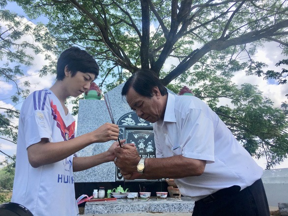 "Ba Cong helps a man light an incense to pray for his deceased family member at ""Tu Thien"" cemetery. Photo: Tuoi Tre"